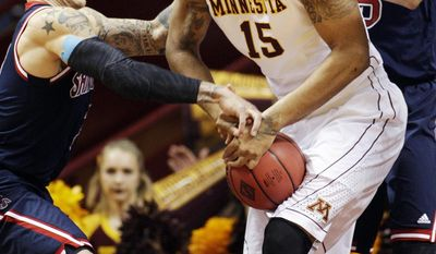 St. Mary's guard Kerry Carter, left, battles for the ball with Minnesota forward Maurice Walker (15) during the first half of an NIT tournament second round game, Sunday, March 23, 2014, in Minneapolis. (AP Photo/Paul Battaglia)