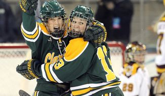 Clarkson's Cayley Mercer, left, and Shelby Nisbet celebrate a goal against Minnesota during the first period an NCAA college hockey game in the finals of the women's Frozen Four in Hamden, Conn., Sunday, March 23, 2014. (AP Photo/Fred Beckham)