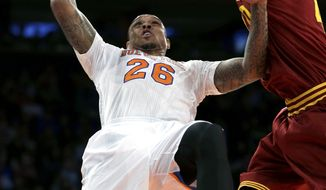 New York Knicks' Shannon Brown, left, puts up a shot while Cleveland Cavaliers' Tyler Zeller defends during the first half of an NBA basketball game at Madison Square Garden, Sunday, March 23, 2014, in New York. (AP Photo/Seth Wenig)