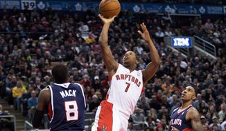 Toronto Raptors guard Kyle Lowry (7) scores past Atlanta Hawks teammates Shelvin Mack (8) and Jeff Teague, right, during the first half of an NBA basketball game in Toronto on Sunday, March 23, 2014. (AP Photo/The Canadian Press, Nathan Denette)