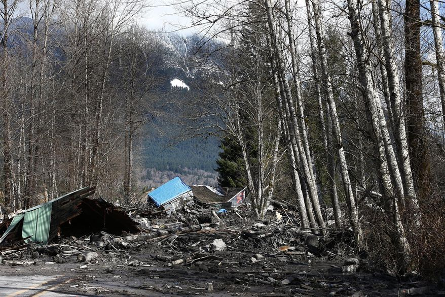 A demolished house sits in the mud on Highway 530, Sunday, March 23, 2014 the day after a giant landslide occurred near Oso, Wash. The slide of mud, trees and rocks happened about 11 a.m. Saturday morning. Several people - including an infant - were critically injured and at least six houses were destroyed. (AP Photo/The Seattle Times, Lindsey Wasson, Pool)