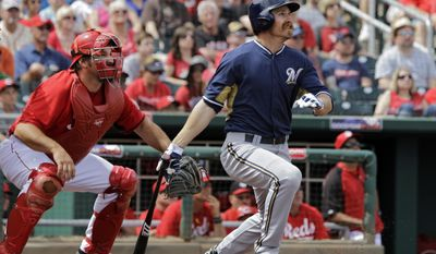 Milwaukee Brewers' Kevin Mattison hits a two-run double as Cincinnati Reds catcher Corky Miller watches, left, in the second inning of a spring exhibition baseball game Sunday, March 23, 2014, in Goodyear, Ariz. (AP Photo/Mark Duncan)