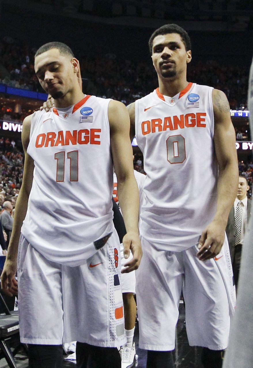 Syracuse's Tyler Ennis (11) and Michael Gbinije (0) leave the court after a third-round game against the Dayton in the NCAA men's college basketball tournament in Buffalo, N.Y., Saturday, March 22, 2014. Dayton won 55-53. (AP Photo/Frank Franklin II)