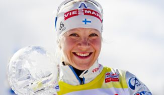 Kaisa Makarainen from Finland holds the trophy after winning the Women's WC 12.5 km biathlon mass start in the Holmenkollen Ski Arena Sunday March 23, 2014, in Oslo, Norway. (AP Photo / Vegard Groett, NTB scanpix) NORWAY OUT