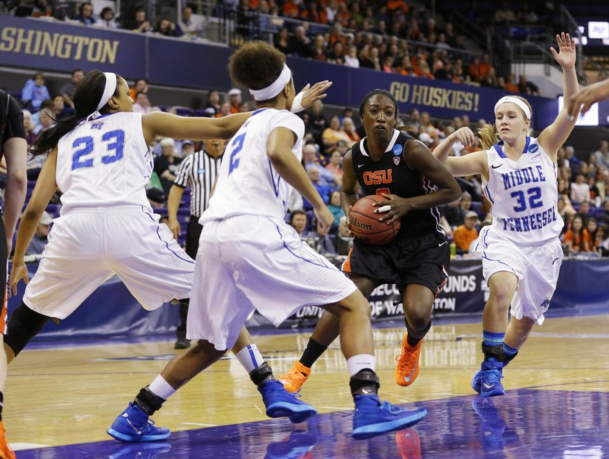 Oregon State's Khadidja Toure, second from right, drives around Middle Tennessee State's Caroline Warden (32) and Janay Brinkley (2) in the first half of a first-round game in the NCAA women's college basketball tournament, Sunday, March 23, 2014, in Seattle. (AP Photo/Ted S. Warren)