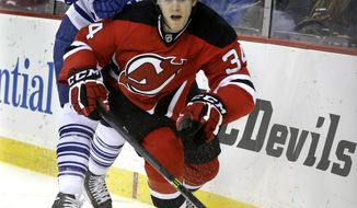 New Jersey Devils' Jon Merrill (34) goes after the puck as he is hit by Toronto Maple Leafs' Nazem Kadri (43) during the first period of an NHL hockey game, Sunday, March 23, 2014, in Newark, N.J. (AP Photo/Mel Evans)
