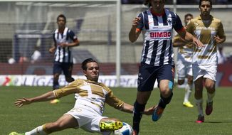 Pumas' Luis Quintana, bottom left, fights for the ball with Monterrey's Omar Arellano during a Mexican soccer league match in Mexico City, Sunday, March 23, 2014. (AP Photo/Christian Palma)