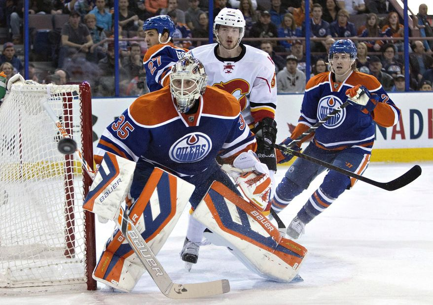 Calgary Flames' Paul Byron (32) looks for the rebound off of Edmonton Oilers goalie Viktor Fasth (35) as Boyd Gordon (27) and Jeff Petry (2) defend during the first period of an NHL hockey game Saturday, March 22, 2014, in Edmonton, Alberta. (AP Photo/The Canadian Press, Jason Franson)