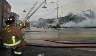 Garrettsville firefighter Ted Stryczny takes a break and watches as several area fire departments work to bring a fire at the intersections of High and Water Streets in downtown Garrettsville. Ohio, under control on Saturday, March 22, 2014. (AP Photo/Akron Beacon Journal, Ed Suba Jr.) MANDATORY CREDIT