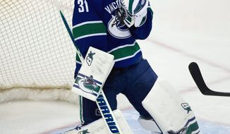 Vancouver Canucks' goalie Eddie Lack, of Sweden, stops a Buffalo Sabres shot during second period NHL hockey action in Vancouver, British Columbia, on Sunday March 23, 2014. (AP Photo/The Canadian Press, Darryl Dyck)