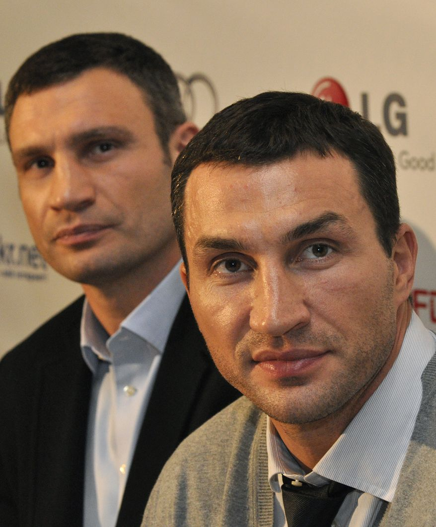 """Ukrainian boxer Vitali Klitschko, left, with his brother Wladimir  responds to questions  in Kiev, Ukraine, Monday, March 12, 2012 during a news conference after the Ukrainian premiere of the documentary """"Klitschko"""" , directed by Sebastian Dehnhardt, which follows their careers  from childhood to heavyweight success. (AP Photo/Sergei Chuzavkov)"""