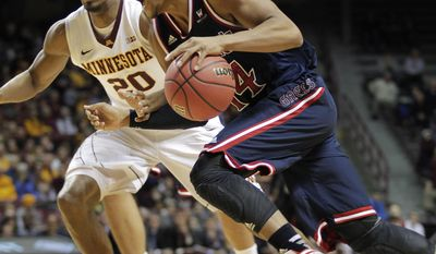 St. Mary's guard Stephen Holt (14) drives against Minnesota guard Austin Hollins (20) during the first half of an NIT tournament second-round game, Sunday, March 23, 2014, in Minneapolis. (AP Photo/Paul Battaglia)