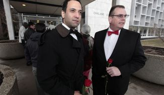 Nasir Khawaja, left, and Mark Sarver stand outside in line to apply for a marriage license at the Oakland County Clerks office in Pontiac, Mich., Saturday, March 22, 2014. A federal judge has struck down Michigan's ban on gay marriage Friday the latest in a series of decisions overturning similar laws across the U.S. Some counties plan to issue marriage licenses to same-sex couples Saturday, less than 24 hours after a judge overturned Michigan's ban on gay marriage. (AP Photo/Paul Sancya)