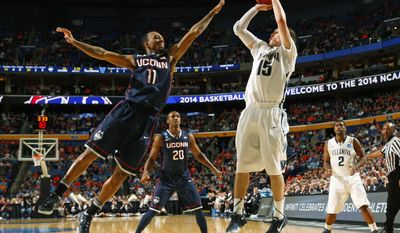 Villanova's Ryan Arcidiacono (15) shoots over Connecticut's Ryan Boatright (11) during the first half of a third-round game in the NCAA men's college basketball tournament in Buffalo, N.Y., Saturday, March 22, 2014. (AP Photo/Bill Wippert)