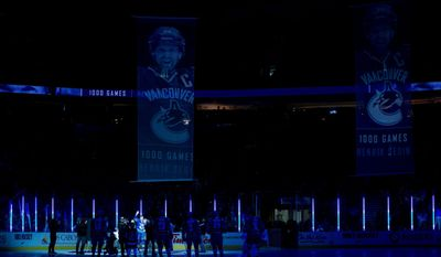 Vancouver Canucks' Henrik Sedin, of Sweden, waves to the crowd as he's honoured for playing 1,000 NHL games before the NHL hockey game against the Buffalo Sabres in Vancouver, British Columbia, on Sunday March 23, 2014. (AP Photo/The Canadian Press, Darryl Dyck)