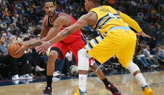 Washington Wizards forward Trevor Ariza, left, looks to pass ball inside as Denver Nuggets guard Randy Foye covers in the first quarter of an NBA basketball game in Denver on Sunday, March 23, 2014. (AP Photo/David Zalubowski)