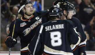 Anaheim Ducks' Ryan Getzlaf, left, and Teemu Selanne, center, congratulate Corey Perry on his goal against the Florida Panthers during the second period of an NHL hockey game, Sunday, March 23, 2014, in Anaheim, Calif. (AP Photo/Danny Moloshok)