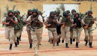 Egyptian security forces members demonstrate their training during a ceremony in Cairo, Egypt, Sunday, March 23, 2014. Egypt's Interior Minister Mohammed Ibrahim observed a parade, feasts and training strategies used by the security forces during the ceremony. (AP Photo/Mohammed Abu Zaid)