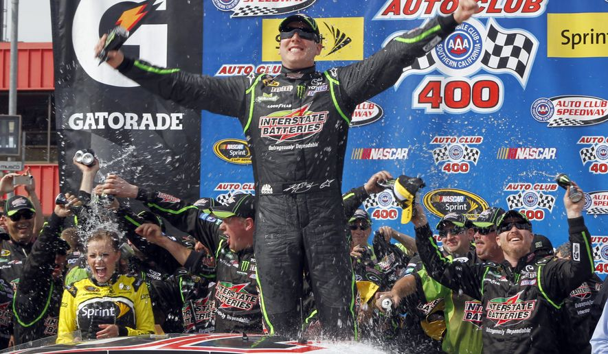 Kyle Busch, center, celebrates, as the team drenches his wife, Samantha Busch, left, in victory circle after winning the NASCAR Sprint Series auto race in Fontana, Calif., Sunday, March 23, 2014. (AP Photo/Alex Gallardo)