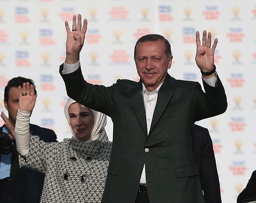 Turkish Prime Minister Recep Tayyip Erdogan, right, addresses supporters of his Justice and Development Party during a rally in Istanbul, Turkey, Sunday, March 23, 2014. Turkish fighter jets shot down a Syrian warplane after it violated Turkey's airspace Sunday, Erdogan said, in a move likely to ramp up tensions between the two countries already deeply at odds over Syria's civil war. Erdogan is fighting corruption allegations against his government a week before local elections that are seen as a referendum over his rule. His wife Emine Erdogan stands at the left(AP Photo/Emrah Gurel)