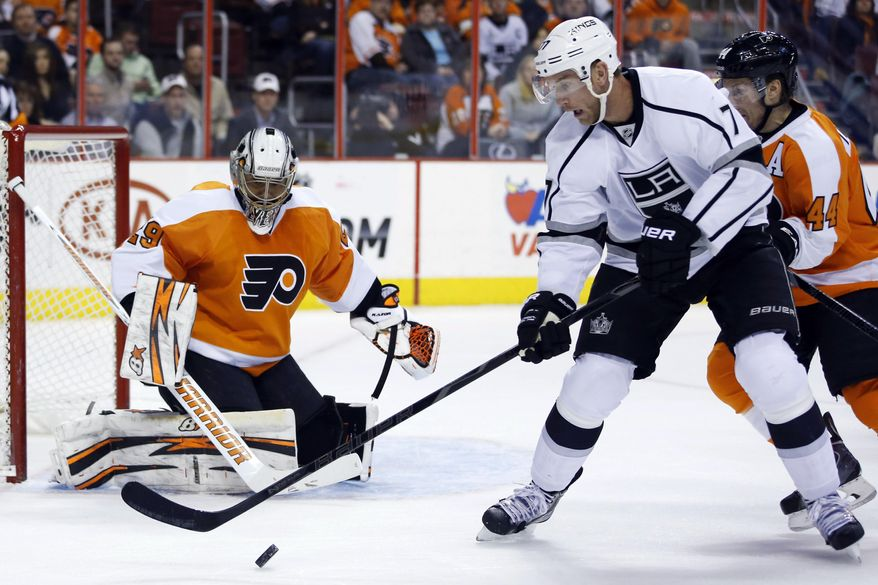 Los Angeles Kings' Jeff Carter (77) tries to settle the puck in front of Philadelphia Flyers' Ray Emery, left, as Kimmo Timonen (44), of Finland, defends during the first period of an NHL hockey game, Monday, March 24, 2014, in Philadelphia. (AP Photo/Matt Slocum)