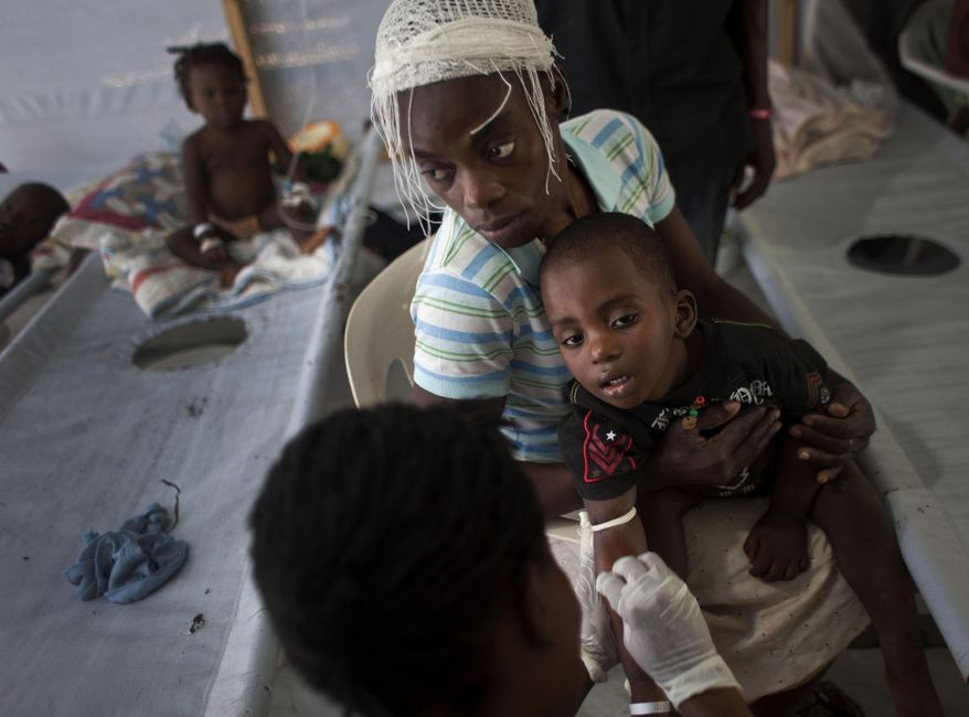 FILE - In this Oct. 19, 2011, file photo, a woman holds her sick child while he receives treatment for cholera at a Doctors Without Borders, MSF, cholera clinic in Port-au-Prince, Haiti. Top U.N. envoy Sandra Honore said this Monday March 24, 2014, that Haiti's cholera outbreak is still the worst in the world. Health officials in Haiti say the epidemic has killed more than 8,000 people. (AP Photo/Ramon Espinosa, File)