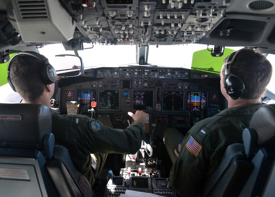 Lt. j.g. Kyle Atakturk, left, and Lt. j.g. Nicholas Horton, naval aviators assigned to Patrol Squadron (VP) 16, pilot a P-8A Poseidon during a March 19, 2014 mission to assist in search and rescue operations for Malaysia Airlines flight MH370. VP-16 is deployed in the U.S. 7th Fleet area of responsibility supporting security and stability in the Indo-Asia-Pacific region. (U.S. Navy photo by Mass Communication Specialist 2nd Class Eric A. Pastor/Released)