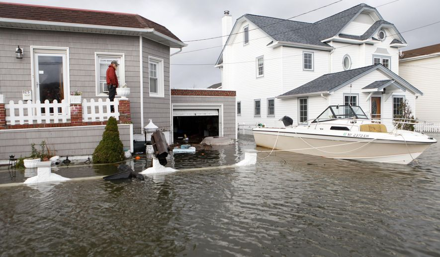 FILE - In this Oct. 30, 2012 file photo, a boat floats in the driveway of a home in the aftermath of Superstorm Sandy in Lindenhurst, N.Y. While President Barack Obama signed a law Friday, March 21, 2014 that will delay steep increases to flood insurance paid by many, nearly 60,000 policyholders in New York state are among the 1.1 million nationwide who will see their federally subsidized flood insurance premiums rise as part of changes to the National Flood Insurance Program, according to a review of federal data by The Associated Press. (AP Photo/Jason DeCrow, File)