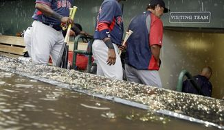 Boston Red Sox designated hitter David Ortiz, left, and teammates exit the dugout after rain canceled the spring exhibition baseball game against the Baltimore Orioles in the second inning in Sarasota, Fla., Monday, March 24, 2014. (AP Photo/Carlos Osorio)