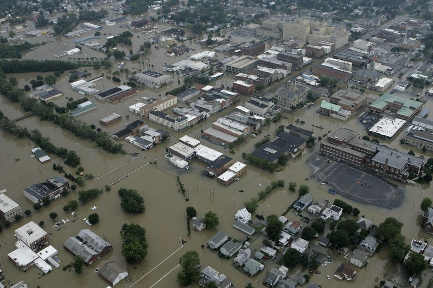 FILE - This Aug. 22, 2007 aerial photo shows flood waters in downtown Findlay, Ohio. Many home and business owners across Ohio with national flood insurance are likely to be hit with rate increases in 2014. Around 20,000 property owners in the state are among the 1.1 million policyholders nationwide facing higher rates to rescue the debt-ridden National Flood Insurance Program, according to a review of federal data by The Associated Press. (AP Photo/Kiichiro Sato)