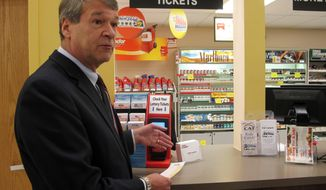 North Dakota Attorney General Wayne Stenehjem demonstrates a new lottery machine at a supermarket in Bismarck, N.D, on Monday, March 24, 2014. The new machines are being placed across the state to allow gamblers to step aside and check their own tickets for winnings without holding up lines. (AP Photo/James MacPherson).