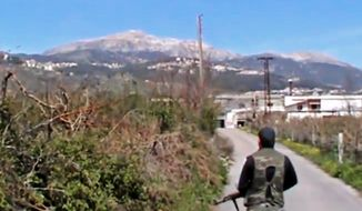 This Sunday, March 23, 2014 image taken from video obtained by the anti-government activist group Shaam News Network, which has been authenticated based on its contents and other AP reporting, shows a Syrian fighter holding his weapon after seizing the predominantly Armenian Christian town of Kassab, Syria. The rebels, including militants from the al-Qaida-affiliated Nusra Front, have also wrested control of a nearby border crossing to Turkey. (AP Photo/Shaam News Network via AP video)