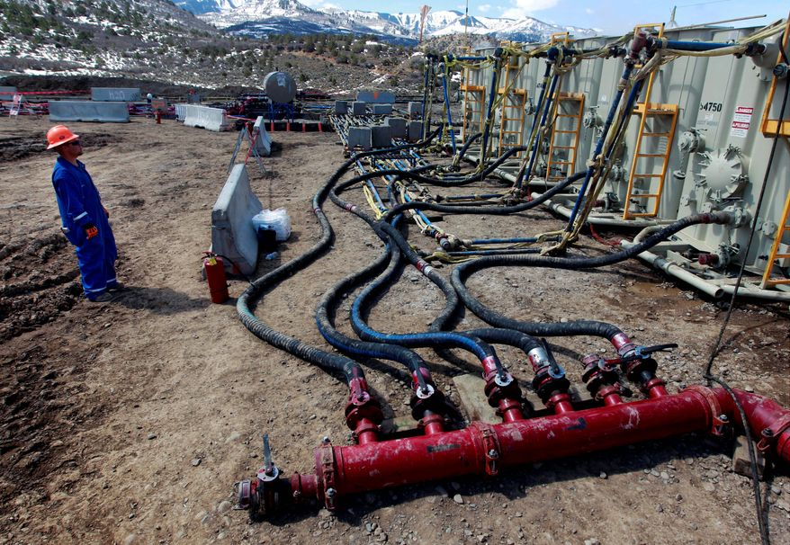 A worker helps monitor water pumping pressure and temperature at a hydraulic fracturing and extraction site outside Rifle, in western Colorado. (Associated Press) ** FILE **
