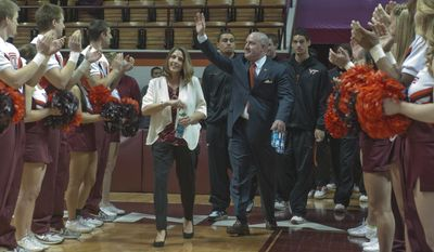 Virginia Tech's new men's head basketball coach, Buzz Williams, enters Cassell Coliseum with his wife Corey,  at an introductory press conference in Blacksburg, Virginia, Monday, March 24, 2014. (AP Photo/Roanoke Times, Don Petersen)