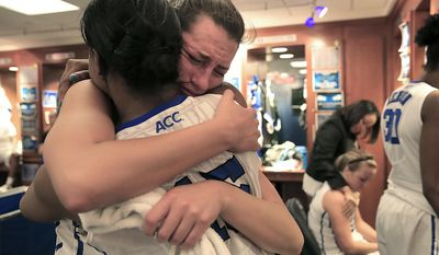 Duke's Haley Peters, facing, hugs teammate Richa Jackson in the locker room, near Duke's Tricia Liston, back right, following Duke's 74-65 loss to DePaul in their second-round game in the NCAA basketball tournament in Durham, N.C., Monday, March 24, 2014.  (AP Photo/Ted Richardson)