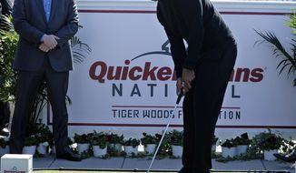 Tiger Woods, center, putts during a putting challenge at the Newseum in Washington, Monday, March 24, 2014. Woods and Quicken Loans Chief Executive Officer Bill Emerson, left, participated in the putting challenge to have the mortgage payments paid for three military families for one month. Earlier, Woods and Emerson announced that Quicken Loans had signed a multi-year agreement to become the title sponsor of the Quicken Loans National to be played at Congressional in Bethesda, Md., in June. (AP Photo/Susan Walsh)