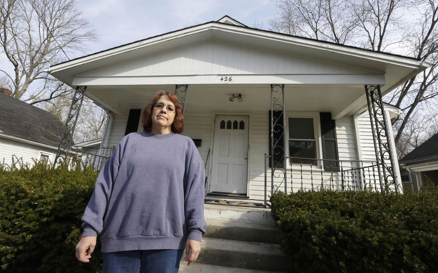 Regina Bachman stands outside her home that has a small creek running behind it in Loveland, Ohio on Friday, March 21, 2014. Bachman bought the home in September 2013 and was initially told by the bank that flood insurance on the property would be affordable, only to find out after closing that the rates were going to increase over $7,000 more annually with new premiums for the National Flood Insurance Program. (AP Photo/Al Behrman)