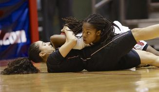 Florida State's Cheetah Delgado, left, and Stanford's Lili Thompson, right, struggle for the ball in the first half of a second-round game in the NCAA women's college basketball tournament in Ames, Iowa, Monday, March 24, 2014. (AP Photo/Nati Harnik)