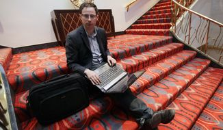 **FILE** Statistician Nate Silver sits on the stairs at Allegro hotel in downtown Chicago on Nov. 9, 2012. (Associated Press)
