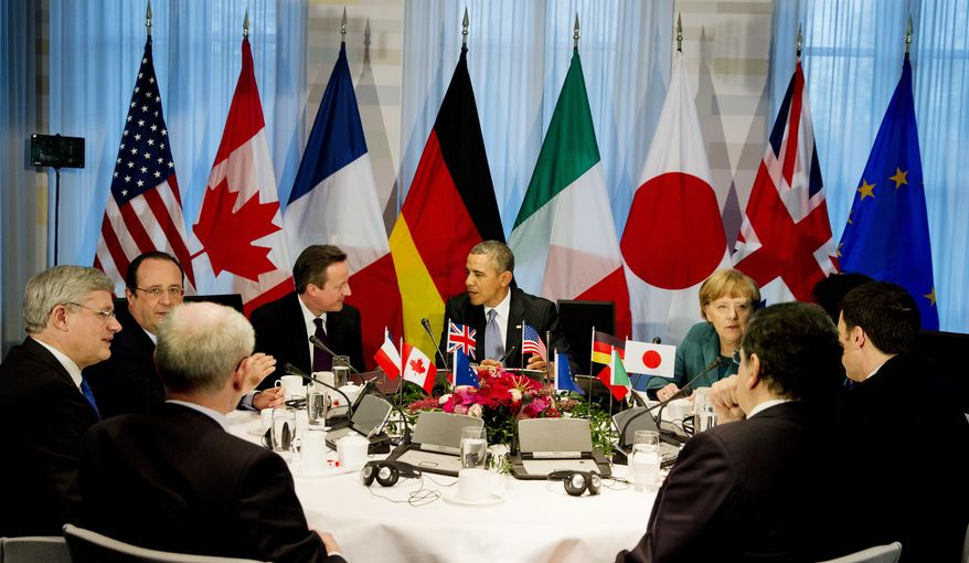 President Barack Obama, center rear, gathered with G7 world leaders clockwise from center left, European Council president Herman Van Rompuy, Canadian Prime Minister Stephen Harper, French President Francois Hollande, British Prime Minister David Cameron, US President Barack Obama, German Chancellor Angela Merkel, Japanese Prime Minister Shinzo Abe, Italian Prime Minister Matteo Renzi and European Commission president Jose Manuel Barroso, in The Hague, Netherlands, Monday March 24, 2014, in the sidelines of the Nuclear security Summit.  (AP Photo/Jerry Lampen, POOL)
