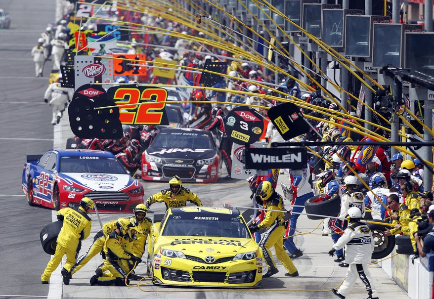 Pole leader Matt Kenseth (20) leads the pack in the first pit stop in the NASCAR Sprint Series auto race in Fontana, Calif., Sunday, March 23, 2014. (AP Photo/Alex Gallardo)