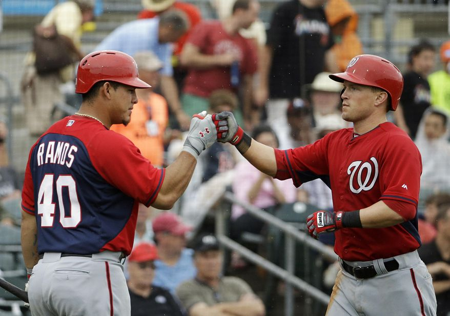 Washington Nationals' Nate McLouth, right, fist-bumps teammate Wilson Ramos after hitting a home run in the sixth inning of an exhibition spring training baseball game against the Miami Marlins, Monday, March 24, 2014, in Jupiter, Fla. (AP Photo/David Goldman)