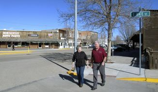 Jeri Widmer, left, and Doug Hamilton, with the Three Valleys Insurance agency, walk down Main Street in Three Forks, Mont. on Thursday, March 20, 2014. The two are among the first in Montana to offer private flood insurance as an alternative to a federal program in which premiums are set to rise up to 25 percent a year. (AP Photo/Matt Volz)