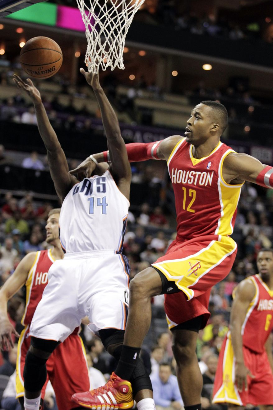 Charlotte Bobcats' Michael Kidd-Gilchrist (14) tries to get his shot off as he is slammed by Houston Rockets' Dwight Howard (12) during the first half of an NBA basketball game in Charlotte, N.C., Monday, March 24, 2014. (AP Photo/Bob Leverone)