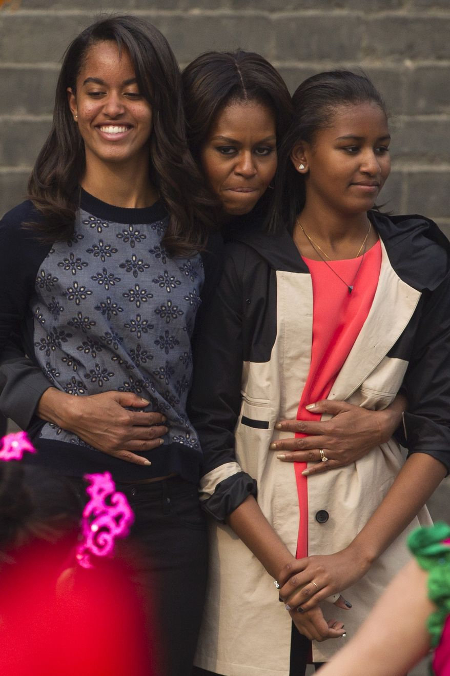 U.S. first lady Michelle Obama, center, hugs her daughters Malia, left, and Sasha, right, when they watch a performance during their visit to an ancient city wall in Xi'an, in northwestern China's Shaanxi province, Monday, March 24, 2014. (AP Photo/Alexander F. Yuan)
