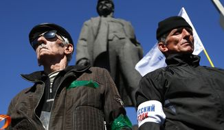 Activists stand guard during a pro Russian rally at a central square in Donetsk, eastern Ukraine, Sunday, March 23, 2014. About 5,000 people demonstrated in Donetsk in favor of holding a referendum on secession and absorption into Russia similar to Crimea's. A statue of Lenin, Soviet Union's first president,  is seen in the background. (AP Photo/Sergei Grits)