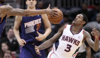 Atlanta Hawks guard Louis Williams (3) and Phoenix Suns forward Marcus Morris, left, fight for a loose ball in the first half of an NBA basketball game Monday, March 24, 2014, in Atlanta. (AP Photo/Jason Getz)