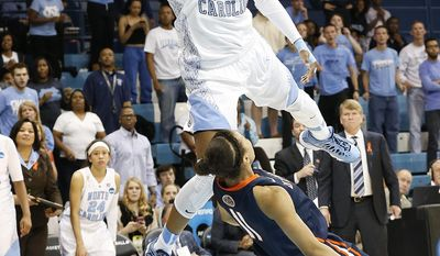 North Carolina's Diamond DeSheilds, left, goes to the basket against UT-Martin's Heather Butler during the second half of a first-round game of the NCAA women's college basketball tournament, Sunday, March 23, 2014, in Chapel Hill, N.C. North Carolina won 60-58. (AP Photo/Ellen Ozier)