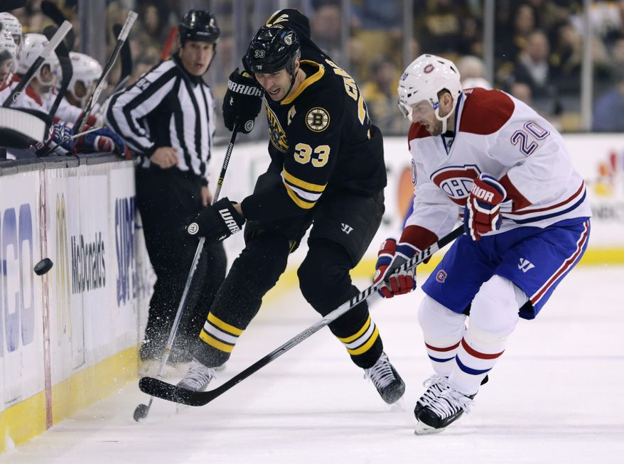 Boston Bruins defenseman Zdeno Chara (33) and Montreal Canadiens left wing Thomas Vanek (20) chase the puck during the first period of an NHL hockey game, Monday, March 24, 2014, in Boston. (AP Photo/Charles Krupa)