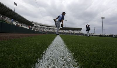 Tampa Bay Rays pitcher Adam Liberatore warms up on a tarp-covered field under the threat of a rain delay before an exhibition baseball game against the Minnesota Twins in Fort Myers, Fla., Monday, March 24, 2014. (AP Photo/Gerald Herbert)